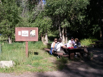 Four people sit and visit at a picnic table.