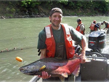 Fisherman in motor boat holding large salmon and smiling