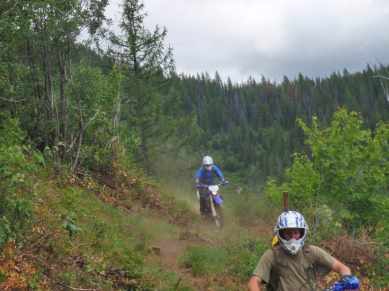 Two dirt bikers riding a trail