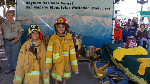 Two children wearing adorably large firefighting nomex turnout jackets