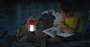 young girl reading a book by lantern light while sitting on a rock