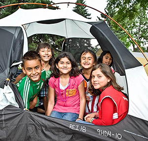 group of kids sticking their heads out of a tent