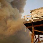 Photo of a lookout tower with a smoke plume near it.
