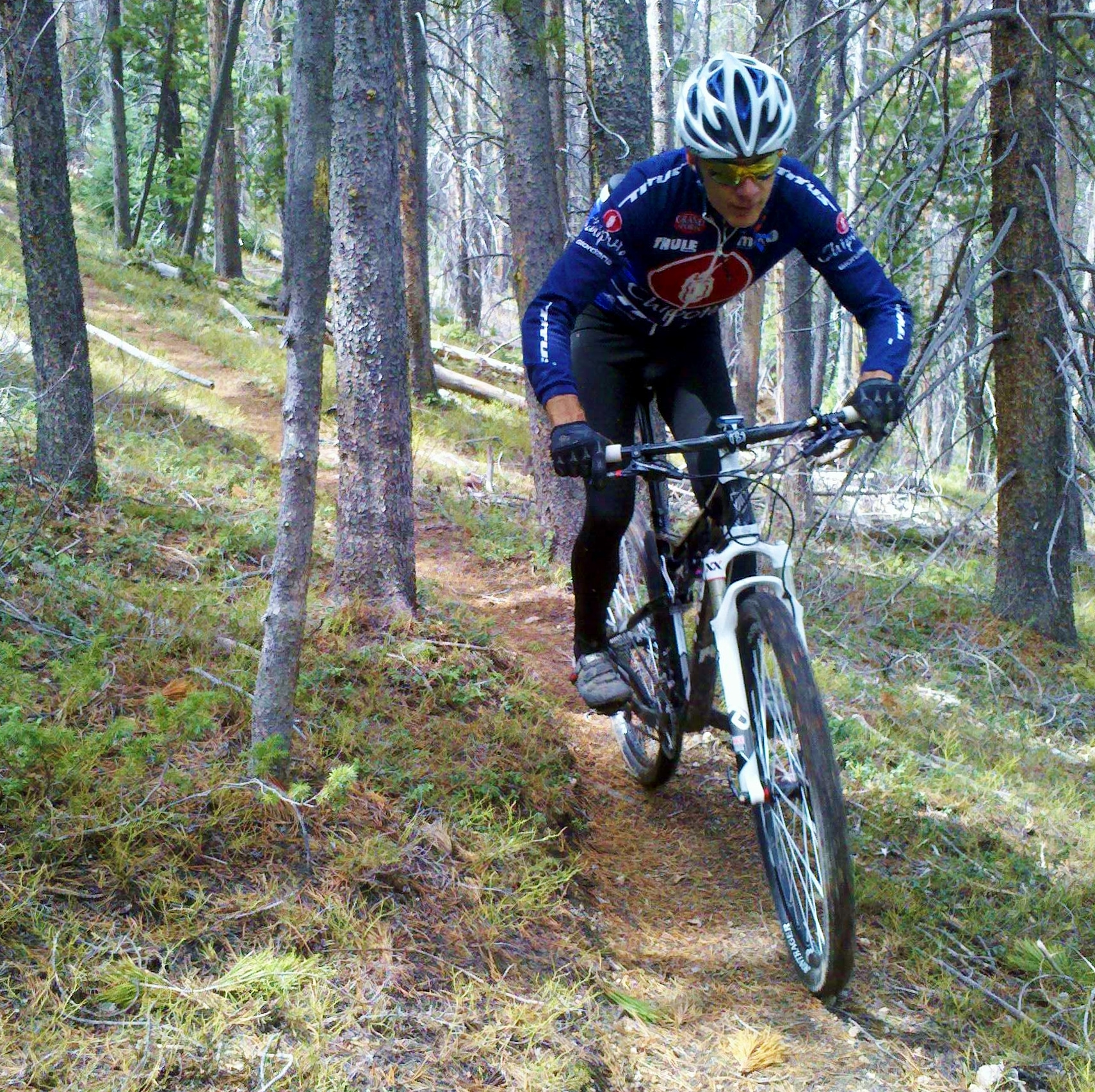 Man moutnain bikes down narrow trail through trees