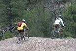 Two mountain bicyclists peddle along a trail