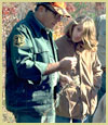 [photo] Forest Service employee in uniform assisting a person.