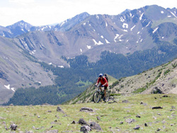 Photo of a mountain biker and a spectacular view of mountains and sky in the background.