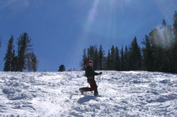 Photo of a skier telemarking on a snowy slope.