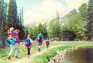 Photo of adults and kids hiking on a path adjacent to a lake