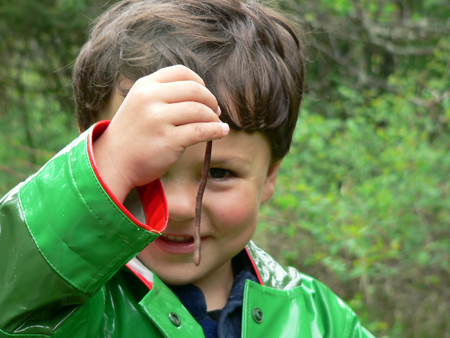 Young boy investigating an earthworm