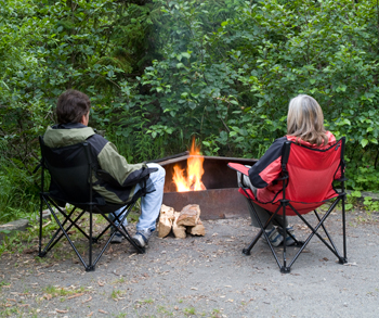 two people around the campfire in a campground