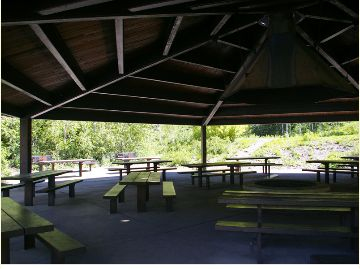 Photo of the picnic pavilion with tables and a fire ring in the middle.