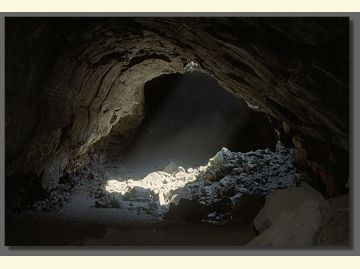 Large cave with light pouring in from hole above