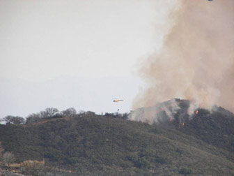 [Photograph]: Helicopter igniting brush with the helitorch mounted below it.