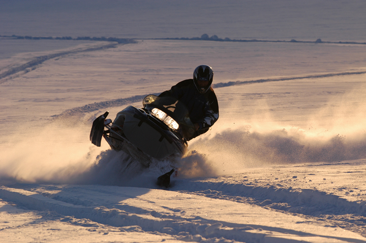 Image of a snowmobile plowing through deep snow