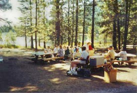 A group enjoys the sunshine and a picnic at Juanita Lake.