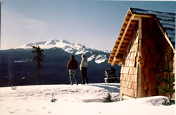 Fuji Shelter with skiers overlooking hill to snow covered mountains in background