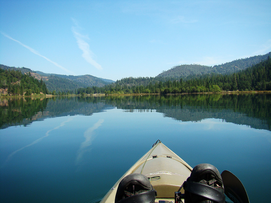 photo shows the front end of a kayak on tranquil lake