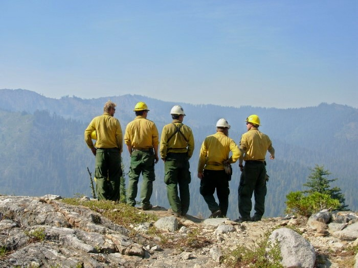 Fire fighters on top of a ridge study the terrain below.