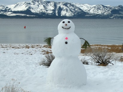 A snowman sits in front of beautiful Lake Tahoe with a snow covered Mount Tallac in the background.