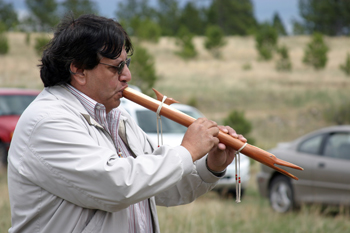 Donovin Sprague plays an instrument at the Lakota Reburial Ceremony