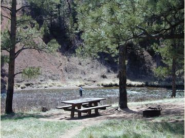Person fishing in river with picnic table in foreground.