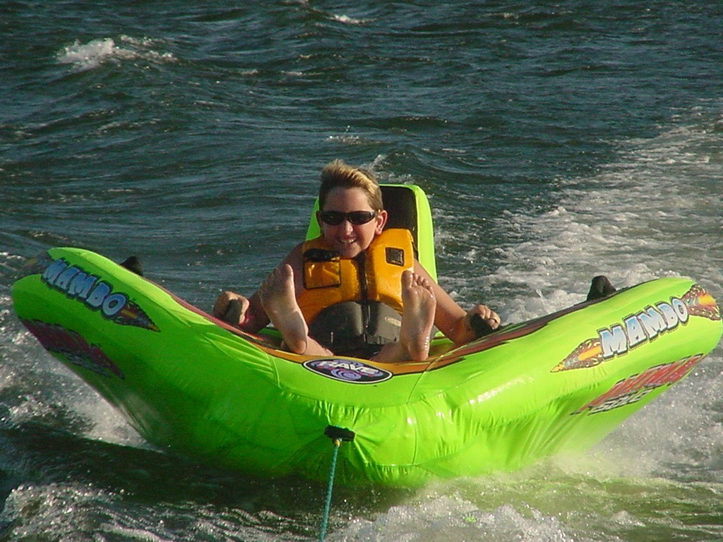 A boy tubing in a bright green tube behind a boat