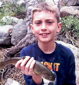 Young boy holding a small trout he caught while fishing in the San Bernardino National Forest