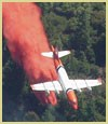 Photo of an air tanker dropping fire retardant on a fire.