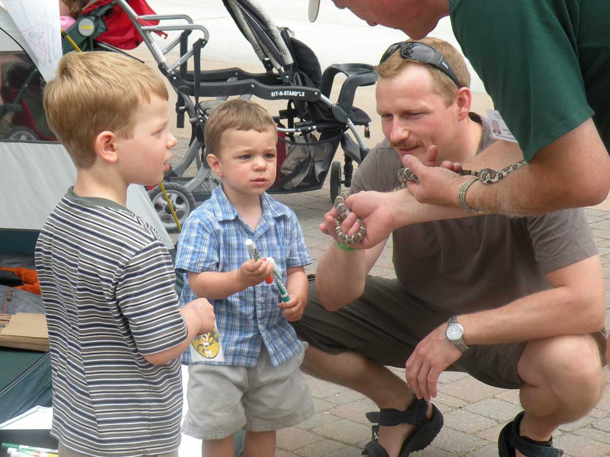 picture from Get Outdoors Day 2010 at Greenfield Village in Dearborn, MI.  A father with two soons being shown a snake native to MI.