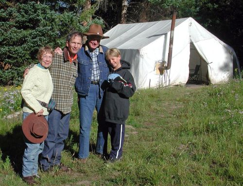 Photo of an outfitter guide camp with people posed near the tent.