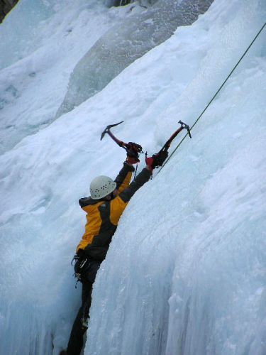 man climgin up over ledge with ice axe