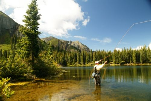 man fly fishing  on shore of lake