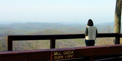 Photo from Mill Creek Overlook. A young lady in the foreground looks across the rolling mountains.