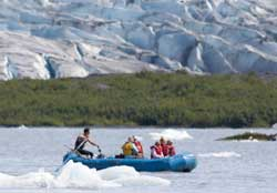 Rafters and their guide drift across Spencer lake with the Glacier in the background