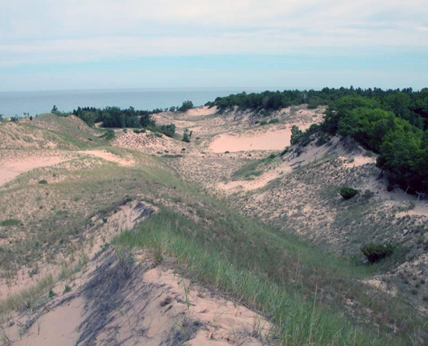 Nordhouse Dunes Wilderness Area - view of the dunes from the top of a hill with Lake Michigan in the distance.