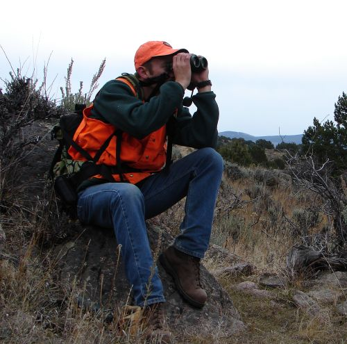 hunter lookign off through binoculars