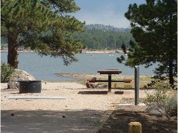A lake sits behind a campsite with a picnic table and trees.