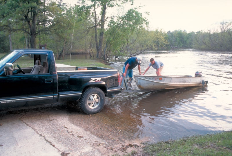 Men unload boat into lake