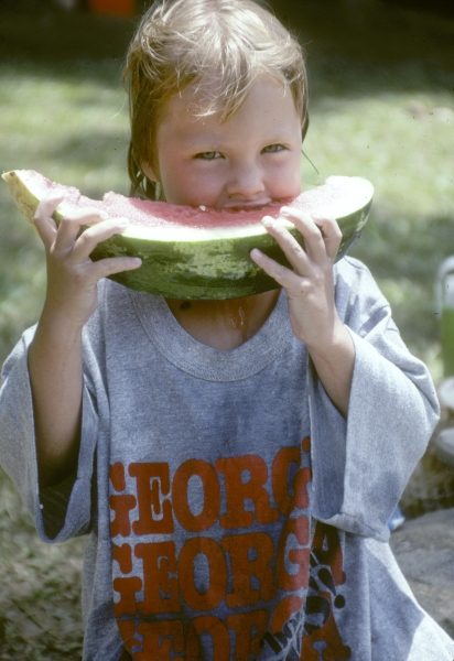 Child enjoying watermelon after a swim