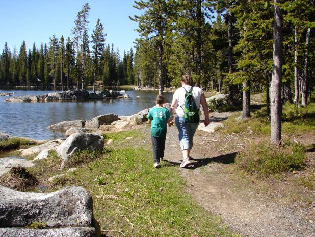 Teenager girl and small boy hiking on a trail by a mountain lake