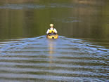 Solo kayaker on Siltcoos River with just ripples from the kayak in smooth water