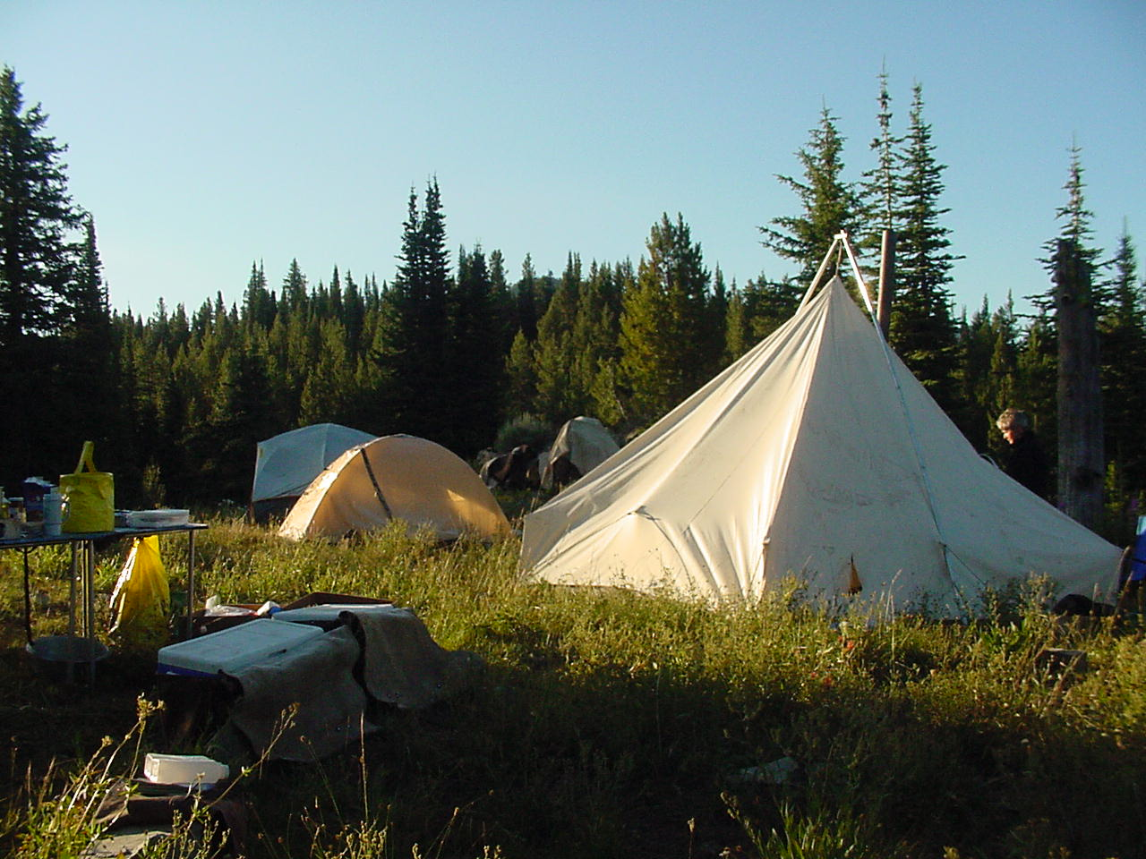 Wilderness camp with wall tents, tables and other gear