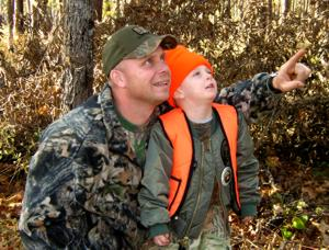 Father and son in hunting gear poingting and looking up in a tree