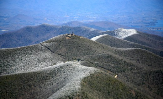 Photo of Brasstown Bald in winters. Mountains surrounding Brasstown Bald covered in snow with Visitor center and firetower as focal point.
