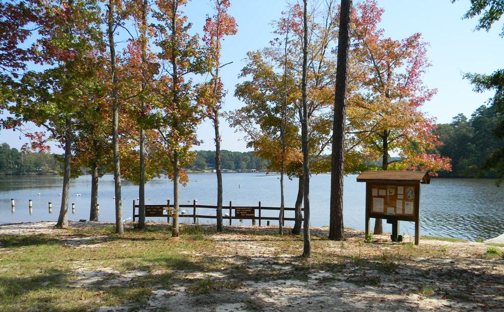 View through trees to the beach area and Kiosk at Lake Sinclair Recreation Area
