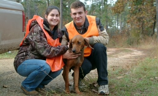 Photo for the Hunting landing page. A couple and their dog happily prepare for a day of hunting.