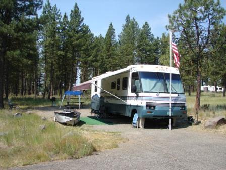 Large RV camper in a pine forest campground with Amercian flag out front