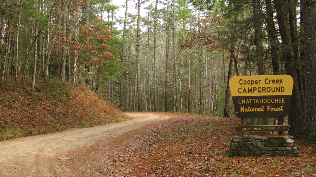 Cooper Creek portal sign sits perched alongside a winding gravel road at entry to campground