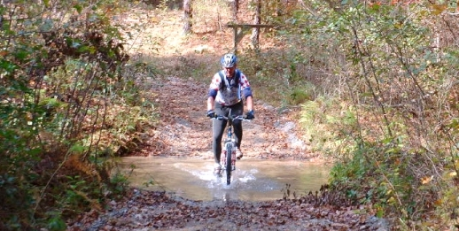 Mountain Biking landing photo. A mountain biker enjoys the scenery and trail as he crosses a stream at Frady Branch.